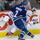 Vancouver Canucks' Dan Hamhuis (2) checks Montreal Canadiens' David Desharnais during the second period of an NHL hockey game, Thursday, Oct. 30, 2014 in Vancouver, British Columbia. (AP Photo/The Canadian Press, Darryl Dyck)
