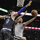 San Antonio Spurs guard Manu Ginobili, right, of Argentina, shoots against Orlando Magic center Nikola Vucevic during the first half of an NBA basketball game on Saturday, March 8, 2014, in San Antonio The Associated Press