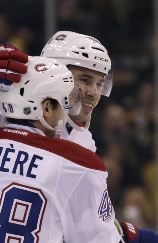 Montreal Canadiens defenseman Alexei Emelin, rear, is congratulated by teammate Daniel Briere after his goal during the first period of an NHL hockey game, Monday, March 24, 2014, in Boston