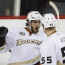 Anaheim Ducks' Mathieu Perreault, left, celebrates his game tying goal with teammate Bryan Allen during third period NHL hockey action against the Calgary Flames in Calgary, Alberta, Wednesday, March 26, 2014. The Anaheim Ducks beat the Calgary Flames 3-2