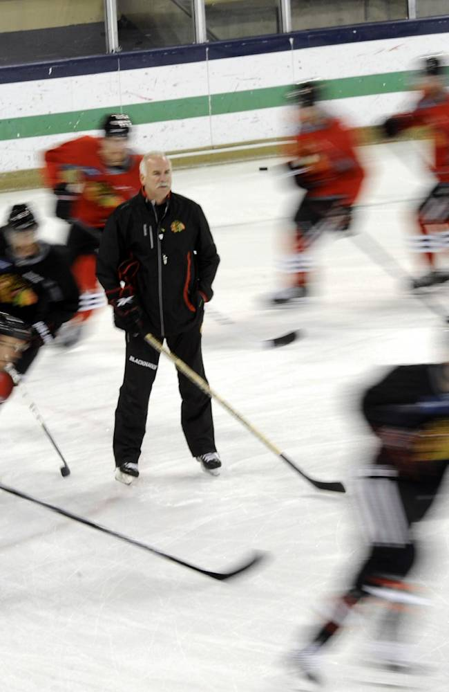 Chicago Blackhawks players skate past coach Joel Quenneville at the teams NHL hockey training camp on the campus of the University of Notre Dame in South Bend, Ind., Thursday, Sept. 12, 2013