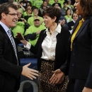 Connecticut head coach Geno Auriemma, left, shakes hands with Notre Dame assistant coach Carol Owens as head coach Muffet McGraw, center, smiles before an NCAA college basketball game, Monday, March 4, 2013, in South Bend, Ind. (AP Photo/Joe Raymond)