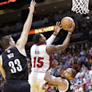 Miami Heat guard Mario Chalmers (15) is charged with an offensive foul as he goes up for a shot against Brooklyn Nets forward Mirza Teletovic (33) of Bosnia, and forward Alan Anderson, right, during the first half of an NBA basketball game, Tuesday, April