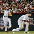 St. Louis Cardinals shortstop Rafael Furcal, left, makes a throw over third baseman David Freese but Washington Nationals' Ian Desmond was safe at first during the sixth inning of a baseball game, Thursday, Aug. 30, 2012, in Washington. The Nationals won 8-1. (AP Photo/Alex Brandon)