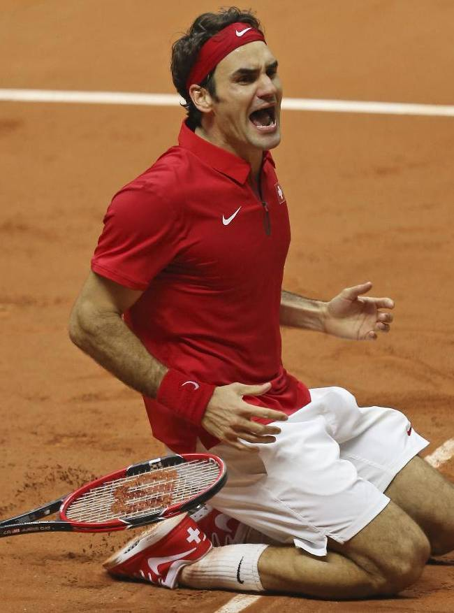 In this Sunday, Nov. 23, 2014 file photo, Switzerland's Roger Federer falls to the clay after defeating France's Richard Gasquet and winning the Davis Cup final for Switzerland at Stade Pierre Mauroy in Lille, northern France. In a career laden with grand slam success, the Davis Cup was a notable absentee from Federer's trophy cabinet. Alongside Stan Wawrinka, Federer helped Switzerland win the team tournament for the first time