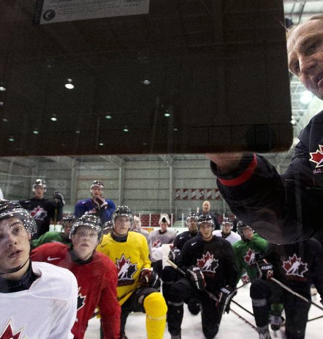 Team Canada head coach Brent Sutter, right, explains a drill to players during the start of world juniors selection camp in Toronto on Friday, Dec. 13, 2013