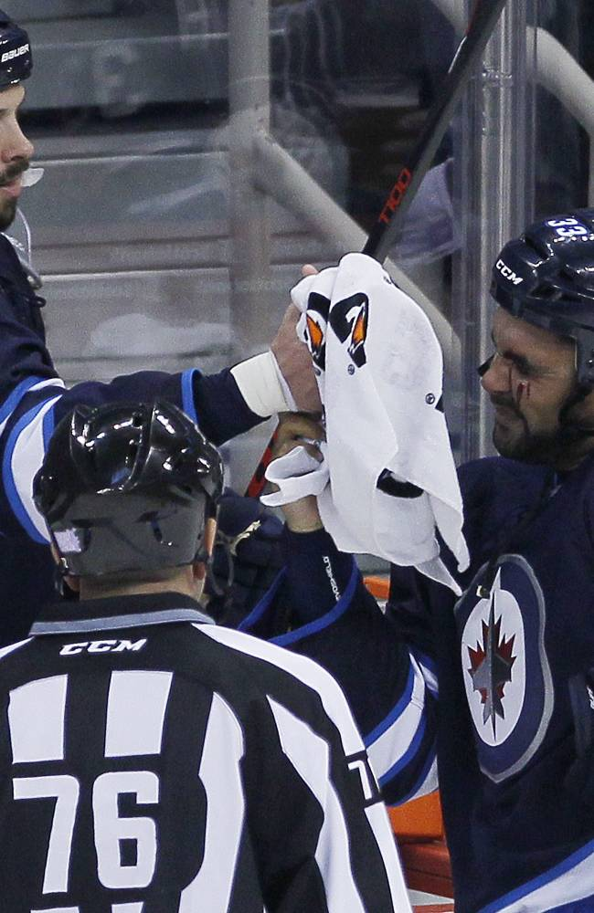 Winnipeg Jets' Dustin Byfuglien (33) is handed a towel for his bleeding eye by teammate Zach Bogosian (44) during first-period NHL hockey game action against the Dallas Stars in Winnipeg, Manitoba, Friday, Oct. 11, 2013