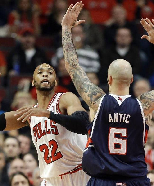 Chicago Bulls forward Taj Gibson (22), left, looks to pass against Atlanta Hawks center Pero Antic (6) during the first half of an NBA basketball game in Chicago on Saturday, Jan. 4, 2014