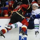 Vancouver Canucks' Radim Vrbata, right, is checked into the boards Calgary Flames' Lance Bouma during second period NHL hockey action in Calgary, Alberta, Wednesday, Oct. 8, 2014 The Associated Press