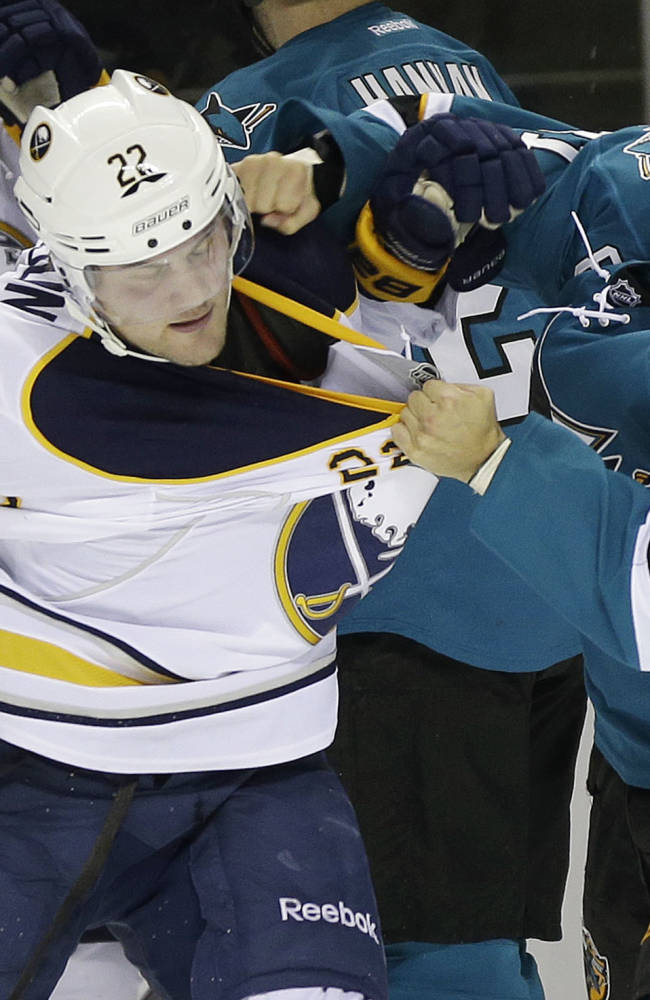 San Jose Sharks' Tyler Kennedy (81), right, fights with Buffalo Sabres' Johan Larsson (22), of Sweden, during the second period of an NHL hockey game on Tuesday, Nov. 5, 2013, in San Jose, Calif