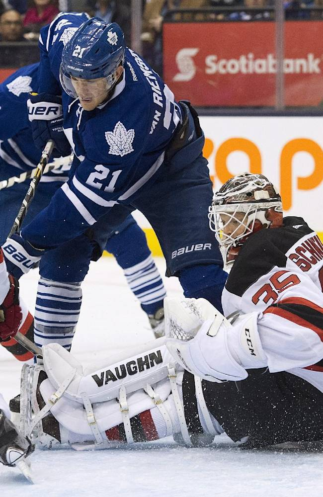 Toronto Maple Leafs forward James van Riemsdyk, left, misses a scoring chance against New Jersey Devils goalie Cory Schneider (35) during second period NHL hockey action in Toronto on Sunday, Jan. 12, 2014