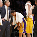Los Angeles Lakers' Steve Nash, center, pauses near the bench, between coach Mike D'Antoni, left, and Steve Blake, right, as the officials review a call at the end of the first half of an NBA basketball game between the Lakers and the Utah Jazz in Los Ang