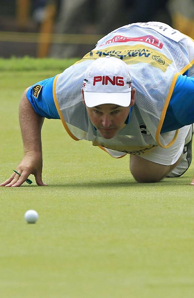Caddie for Lee Westwood of England lines up a putt on the ninth green during the final round of the Malaysian Open golf tournament at Kuala Lumpur Golf and Country Club in Kuala Lumpur, Malaysia, Sunday, April 20, 2014