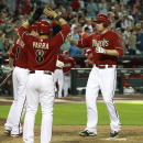 Arizona Diamondbacks' Mark Trumbo, right, is greeted at home plate by teammates A.J. Pollock (11) and Gerardo Parra (8) after hitting a three-run home run against the Los Angeles Dodgers during the seventh inning of a baseball game on Sunday, April 13, 20