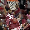 Massachusetts' Raphiael Putney dunks the ball over New Mexico's Alex Kirk in the second half at the Charleston Classic NCAA college basketball tournament in Charleston, S.C., Friday, Nov. 22, 2013. Massachusetts defeated New Mexico 81-65. (AP Photo/Mic Smith)
