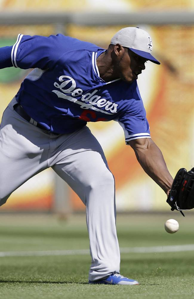 Los Angeles Dodgers right fielder Yasiel Puig cannot make a play on a ball hit by Kansas City Royals' Pedro Ciriaco during the fourth inning of an exhibition baseball game Tuesday, March 11, 2014, in Surprise, Ariz