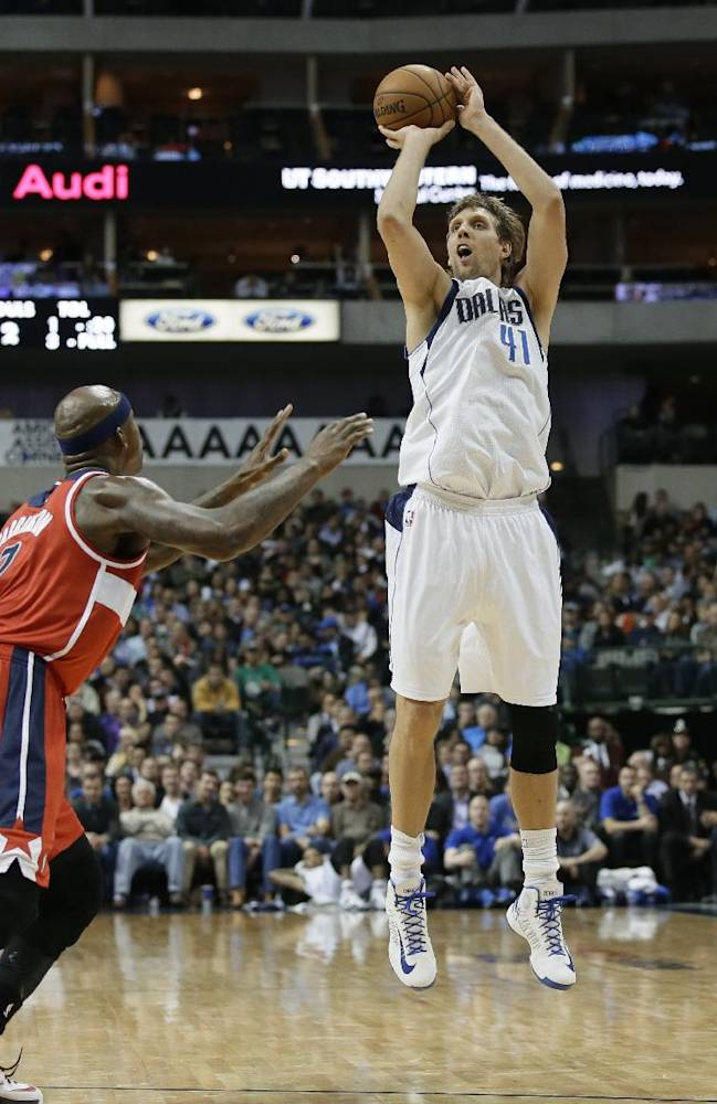 Dallas Mavericks forward Dirk Nowitzki (41) goes up over Washington Wizards' Al Harrington, left, to score a 3-point basket in the second half of an NBA basketball game, Tuesday, Nov. 12, 2013, in Dallas. With that basket Nowitzki passed Jerry West for 16th place on the NBA's all-time scoring list. The Mavericks won 105-95
