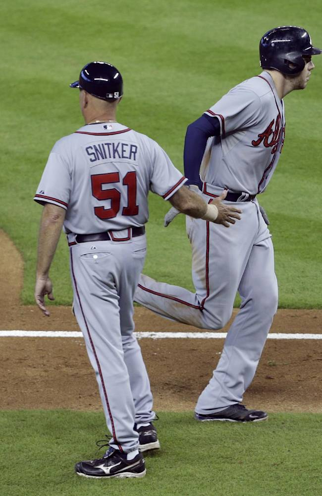 Atlanta Braves' Freddie Freeman, right, is met by third base coach Brian Snitker (51) as he runs the bases after hitting a two-run home run in the fourth inning during a baseball game against the Miami Marlins, Thursday, Sept. 12, 2013, in Miami