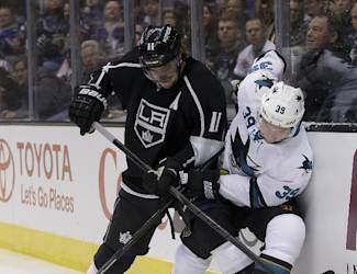 Los Angeles Kings center Anze Kopitar, left, checks San Jose Sharks center Logan Couture during the first period of an NHL hockey game in Los Angeles, Thursday, Dec. 19, 2013. (AP Photo/Chris Carlson)