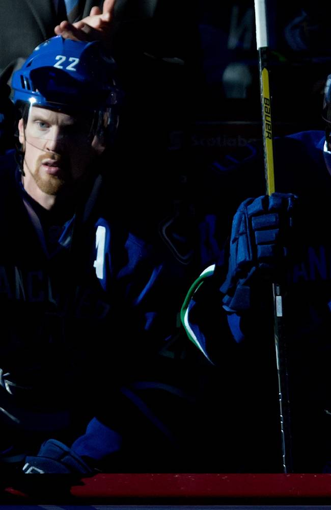 Vancouver Canucks' Daniel Sedin, left, and his twin brother, Henrik Sedin, both of Sweden, sit on the bench as the team's Olympians are honored before the Canucks' NHL hockey game against the St. Louis Blues in Vancouver, British Columbia, on Wednesday, Feb. 26, 2014