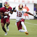 Washington Redskins receiver Andre Roberts (12) plants his foot to try to avoid coverage by cornerback Richard Crawford during practice at the team's NFL football training facility, Sunday, July 27, 2014 in Richmond, Va The Associated Press