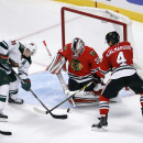 Chicago Blackhawks goalie Antti Raanta (31) makes a save on a shot by Minnesota Wild left wing Zach Parise (11), as defenseman Niklas Hjalmarsson (4) also defends, during the third period of an NHL hockey game Tuesday, Dec. 16, 2014, in Chicago. The Black