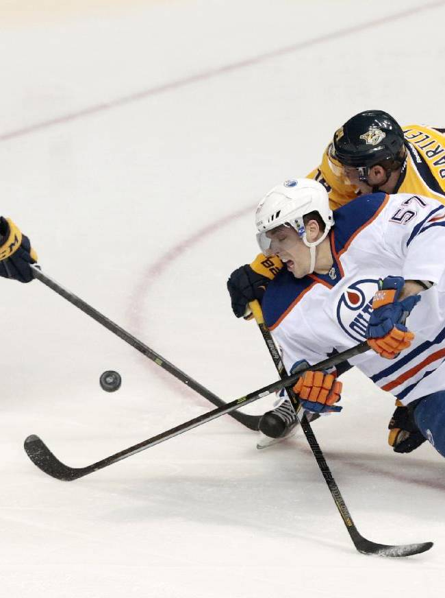 Edmonton Oilers left wing David Perron (57) slips as Nashville Predators defensemen Seth Jones (3) and Victor Bartley (64) slow him down in the first period of an NHL hockey game on Thursday, Nov. 28, 2013, in Nashville, Tenn