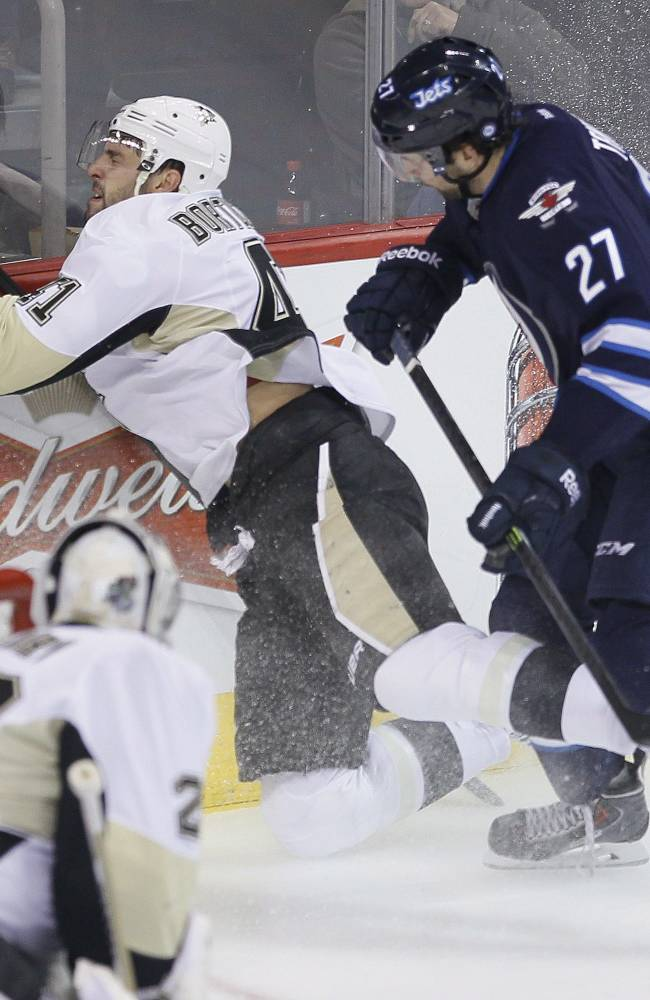 Pittsburgh Penguins' Robert Bortuzzo (41) gets checked into the boards by Winnipeg Jets' Eric Tangradi (27) as Penguins goaltender Marc-Andre Fleury (29) watches during the first period of an NHL hockey game in Winnipeg, Manitoba, on Thursday, April 3, 2014