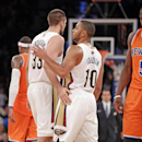 New Orleans Pelicans forward Ryan Anderson (33) and Pelicans guard Eric Gordon (10) celebrate as New York Knicks guard Tim Hardaway Jr. (5) leaves the court after defeating the Knicks 103-99 in an NBA basketball game in New York, Sunday, Dec. 1, 2013 The