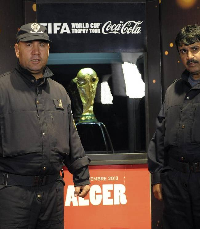 Algerian police officers guard the FIFA World Cup Trophy, Friday, Nov. 22, 2013, in Algiers. The trophy arrived Thursday for a two-day exhibition which will open to the public on Friday.  The soccer mad country Algeria qualified Tuesday for the 2014 World Cup Finals