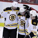 Boston Bruins defenseman Zdeno Chara (33) of the Czech Republic, left, and right wing Reilly Smith (18), congratulate center Patrice Bergeron (37) after his empty net goal during the third period of Game 3 of a first-round NHL hockey playoff series agains