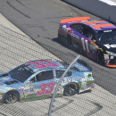 Alex Kennedy (33) spins out on the front stretch as Denny Hamlin (11) passes by during the NASCAR Sprint Cup auto race at Martinsville Speedway in Martinsville, Va., Sunday, March 29, 2015. (AP Photo/Don Petersen)