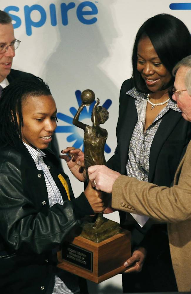 Southern Mississippi guard Jamierra Faulkner, left receives the Gillom Trophy from Rick Cleveland, executive director of the Mississippi Sports Hall of Fame and Museum, right, and the trophy's namesake, former Mississippi player and assistant coach Peggie Gillom-Grandersom, second from right, Monday afternoon, March 3, 2014 at the Mississippi Sports Hall of Fame in Jackson, Miss. The award sponsored by C Spire Wireless, is given to Mississippi's best women's college basketball player. Dave Miller, C Spire Wireless senior manager for media relations, rear left, watches the presentation. (AP Photo /Rogelio V. Solis)