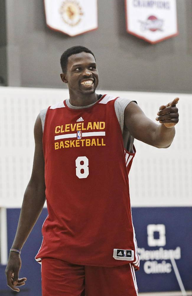 New Cleveland Cavaliers forward Luol Deng walks to his first meeting with reporters at the NBA team's practice facility in Independence, Ohio, Wednesday, Jan. 8, 2014. Cleveland traded Andrew Bynum and future draft choices to the Chicago Bulls for the two-time All-Star on Tuesday