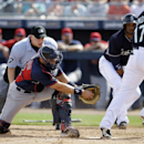 Seattle Mariners' Justin Smoak, right, scores under the attempted tag of Cleveland Indians' Matt Treanor, left, as home plate umpire Scott Barry, rear, watches in the first inning of a spring training baseball game, Wednesday, March 5, 2014, in Peoria, Ar