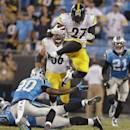 Pittsburgh Steelers' LeGarrette Blount (27) leaps over Carolina Panthers' Antoine Cason (20) during the second half of an NFL football game in Charlotte, N.C., Sunday, Sept. 21, 2014. The Steelers won 37-19. (AP Photo/Bob Leverone)