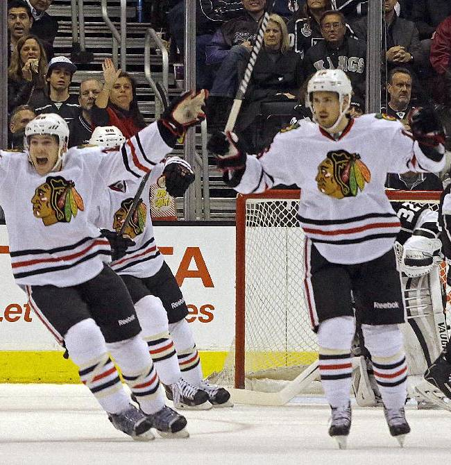 Chicago Blackhawks' Ben Smith (28), left, and defenseman Michael Kostka (6) celebrate a goal by Marcus Kruger, not shown, against Los Angeles Kings goalie Jonathan Quick (32) and defenseman Matt Greene (2) look on in the second period of an NHL hockey game in Los Angeles, Monday, Feb. 3, 2014