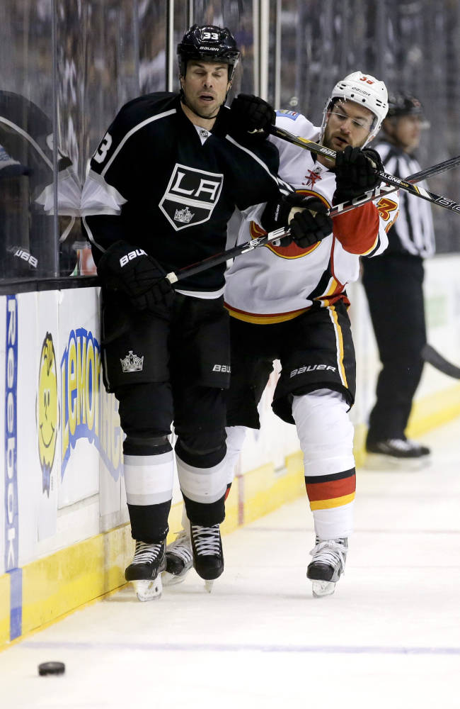 Calgary Flames left wing T.J. Galiardi, right, checks Los Angeles Kings defenseman Willie Mitchell during the first period of an NHL hockey game in  Los Angeles, Monday, Oct. 21, 2013