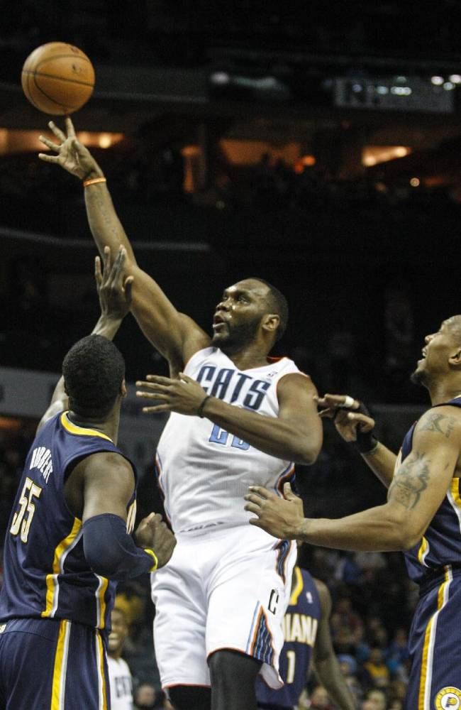 Charlotte Bobcats center Al Jefferson, center, shoots over Indiana Pacers center Roy Hibbert during the first half of an NBA basketball game in Charlotte, N.C., Wednesday, March 5, 2014