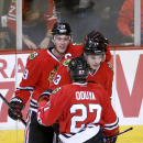 Chicago Blackhawks center Jonathan Toews (19) celebrates this goal with Johnny Oduya (27) and Daniel Carcillo during the second period of an NHL hockey game against the Minnesota Wild, Tuesday, Dec. 16, 2014, in Chicago The Associated Press