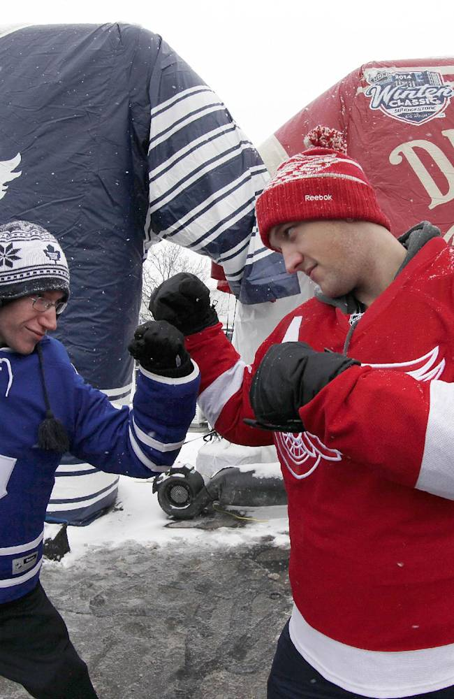 Nathan Dunville, of Halifax, Nova Scotia, left, and Adam Boutilier, of Cole Harbour, Nova Scotia, pose for family photographs at the NHL Winter Classic hockey game at Michigan Stadium in Ann Arbor, Mich., Wednesday, Jan, 1, 2014, where the Detroit Red Wings play the Toronto Maple Leafs