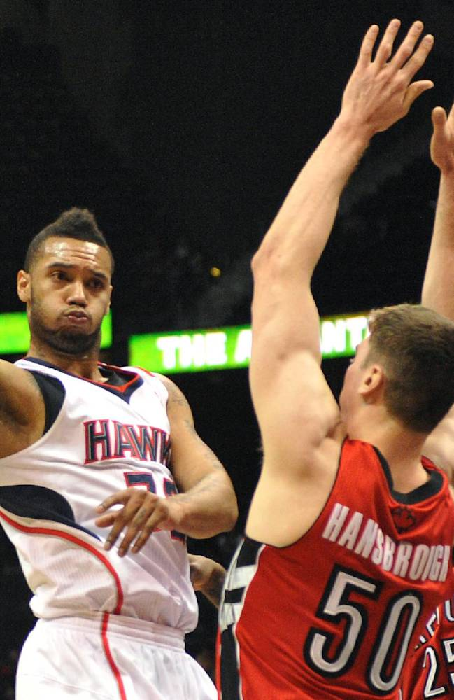 Atlanta Hawks' Mike Scott, left, passes around Toronto Raptors' Tyler Hansbrough (50) and John Salmons (25) in the first half of their NBA basketball game Tuesday, March 18, 2014, in Atlanta