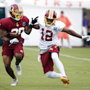 Washington Redskins receiver Andre Roberts (12) plants his foot to try to avoid coverage by cornerback Richard Crawford during practice at the team's NFL football training facility, Sunday, July 27, 2014 in Roanoke, Va The Associated Press