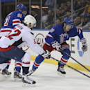 New York Rangers left wing Chris Kreider, right, battles for the puck against Washington Capitals defenseman Mike Green (52) in the second period of an NHL hockey game on Sunday, Dec. 8, 2013, in New York The Associated Press
