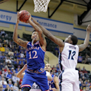 Kansas guard Kelly Oubre Jr., left, shoots over Rhode Island forward Hassan Martin during the first half of an NCAA college basketball game in Lake Buena Vista, Fla., Thursday, Nov. 27, 2014. (AP Photo/Reinhold Matay)