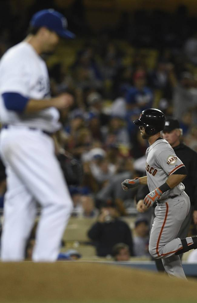 San Francisco Giants' Brandon Hicks, right, runs the bases after hitting a home run off of Los Angeles Dodgers starting pitcher Josh Beckett, front, during the seventh inning of a baseball game in Los Angeles, Thursday, May 8, 2014