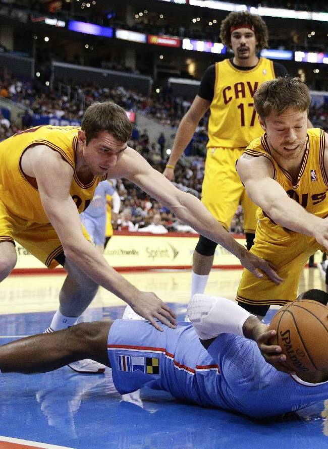 Los Angeles Clippers's Glen Davis, bottom, fights for the ball with Cleveland Cavaliers's Tyler Zeller, left, and Matthew Dellavedova during the first half of an NBA basketball game on Sunday, March 16, 2014, in Los Angeles