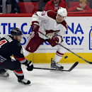 Arizona Coyotes' Lauri Korpikoski (28) of Finland, flips the puck past Carolina Hurricanes' Andrej Sekera (4) of Slovakia, during the third period of an NHL hockey game in Raleigh, N.C., Saturday, Nov. 1, 2014. Hurricanes won 3-0 for their first win of th
