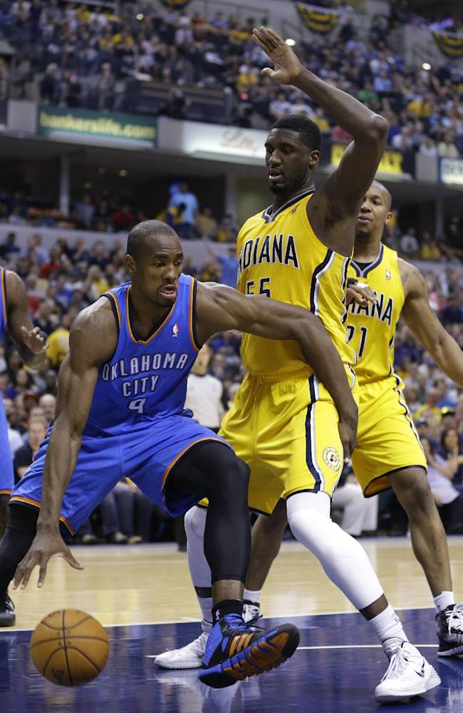 Oklahoma City Thunder forward Serge Ibaka, left, drives around Indiana Pacers center Roy Hibbert in the first half of an NBA basketball game in Indianapolis, Sunday, April 13, 2014