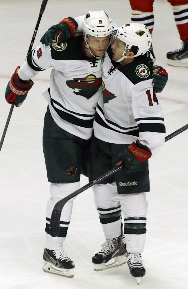 Minnesota Wild's Justin Fontaine (14), right, celebrates with Mikko Koivu (9) after scoring his goal against the Chicago Blackhawks during the third period of an NHL hockey game in Chicago, Saturday, Oct. 26, 2013. The Wild won 5-3